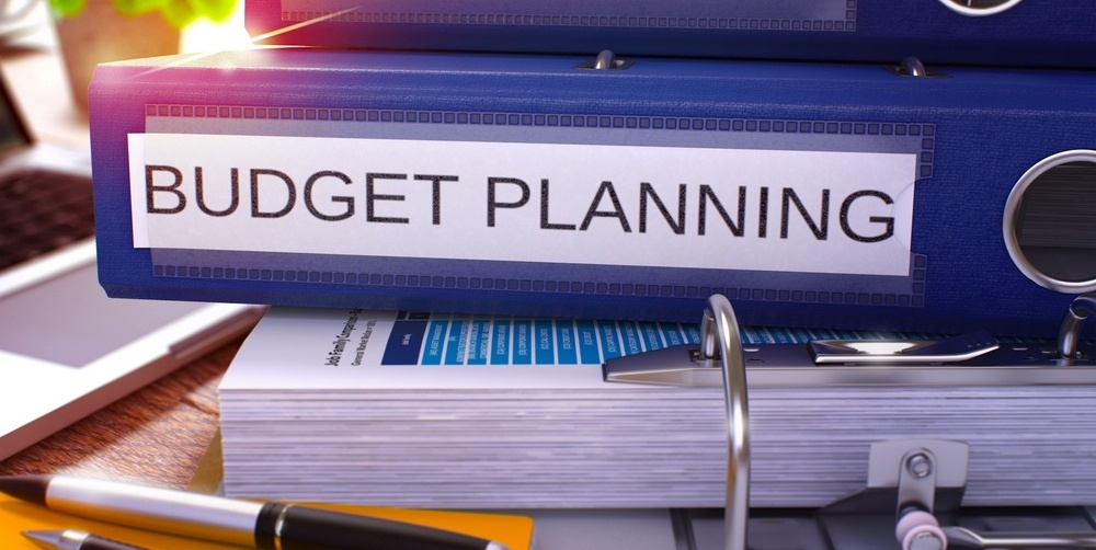 Blue Ring Binder with Inscription Budget Planning on Background of Working Table with Office Supplies and Laptop. Budget Planning Business Concept on Blurred Background. 3D Render.-427851-edited.jpeg