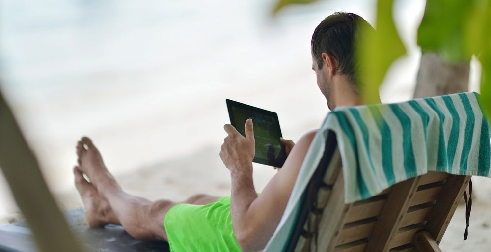 business man relaxing and use tablet computer at beautiful tropical beach-723340-edited.jpeg